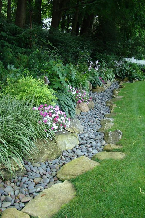 Rocks and plants lining the edge of a yard.